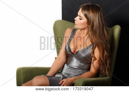 Young sexy woman in evening dress sitting in the chair.