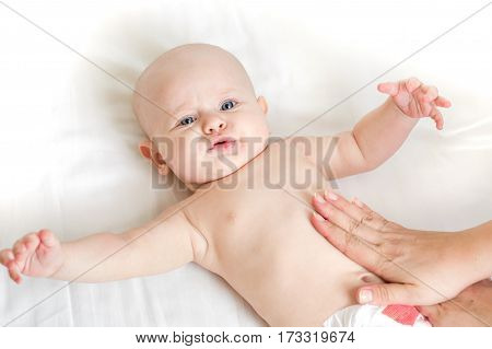 Baby massage lying on the back at home on the bed