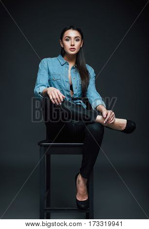 Studio fashion shot: beautiful young woman in jeans and shirt sitting on a bench