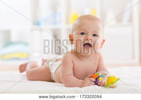 Laying small baby with a toy lying on his belly in nursery room