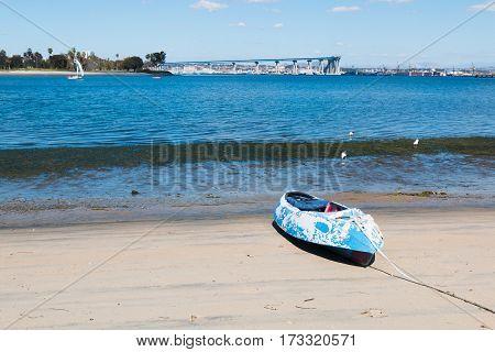 A kayak on the beach of Glorietta Marina Park in Coronado, California, with the San Diego-Coronado Bay Bridge and San Diego Bay in the background.