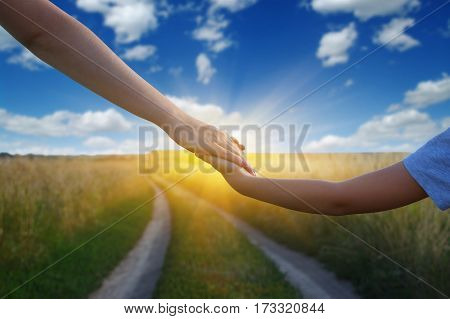 Hands of holding each other in field on road and sun