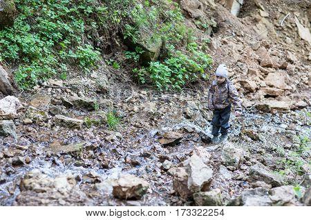 A boy walks on the rocks of a mountain stream.
