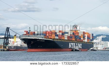 Oakland CA - February 24 2017: Tugboats are vital for safe efficient maneuvering for the large ships in and out of port. Multiple tugboats assist NYK AQUARIUS to maneuver into the Port of Oakland.