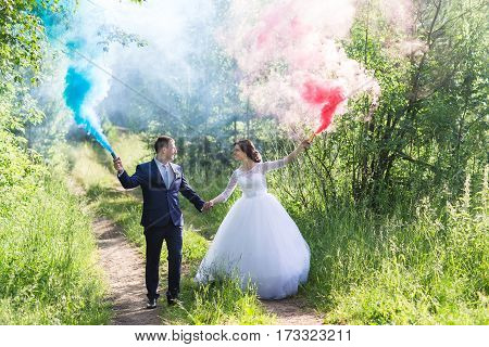 Wedding couple runs blue and pink smoke in the park