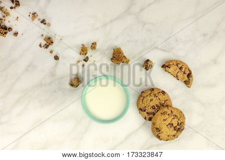 Chocolate chips cookies and crumbs, shot from above on a white marble background, with a glass of milk and a place for text