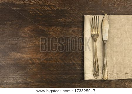 An overhead photo of a vintage fork and knife on a wooden background texture. A restaurant menu or special offer banner design template