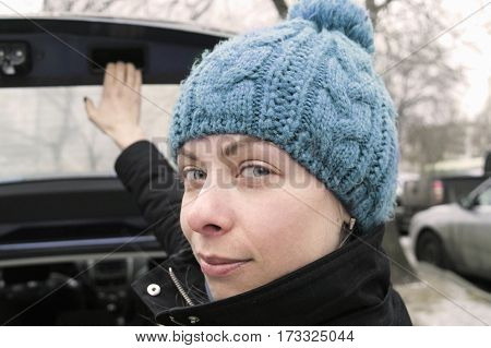 Young female about to open or close a car boot concept of travel by car. Outdoor cropped portrait
