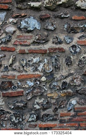 Old wall in England built with flint, Roman bricks and lime mortar, background pattern.