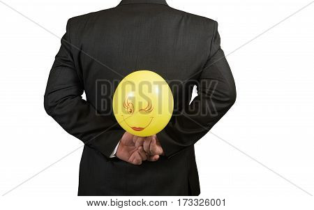 Fool's day is businessman with a balloon behind his back, isolated.