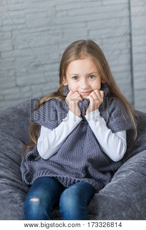 Fashion child knitted sweater in the Studio sitting. The child in a warm jacket.