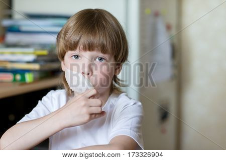 Offending child sits at a table with his mouth sealed with tape. The concept of domestic violence and child protection.