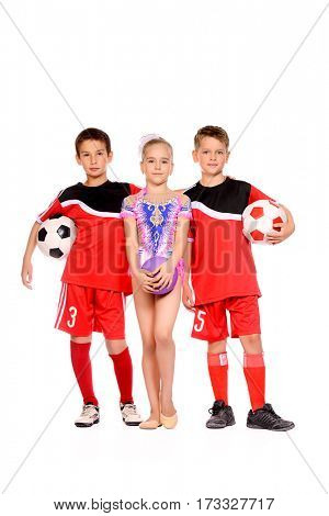 Sports and activities for children. Two boys football players and a girl gymnast posing together. Education. Isolated over white background.