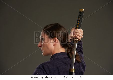 Rear view of young woman taking out katana sword