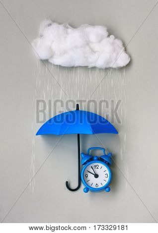 Blue alarm clock under an umbrella on a gray background cumulus clouds rain concept of protection time