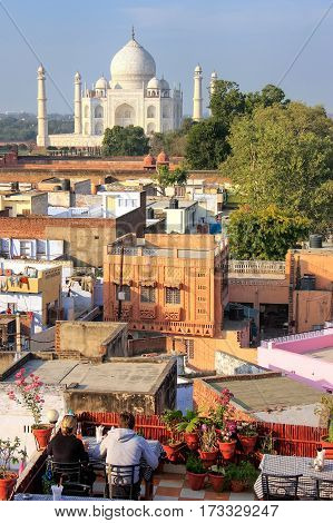 View of Taj Mahal from the rooftop restaurant in Taj Ganj neighborhood in Agra India. Taj Mahal was build in 1632 by Emperor Shah Jahan as a memorial for his second wife Mumtaz Mahal. poster
