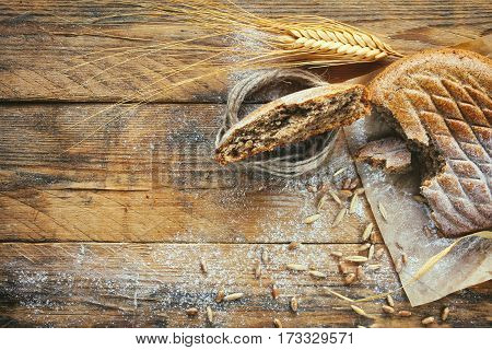 Cereal flapjack ears of wheat and rye corn sprinkled flour on old wooden table rustic style.