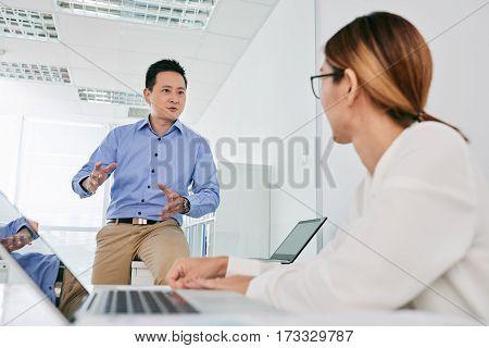 Singaporean businessman explaining his idea to female colleague