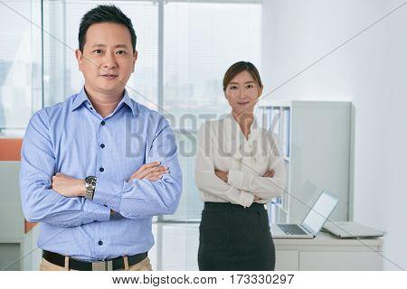 Portrait of confident Singaporean businessman, his colleague standing behind him