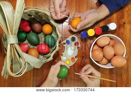 Top view of hands of family members are painting eggs with a paintbrush and palette on wooden table for preparing happy Easter day.