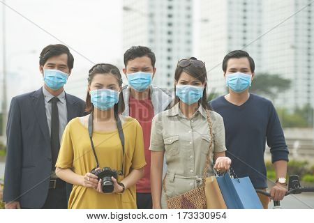Unhappy Asian people with face masks: preventing the flu