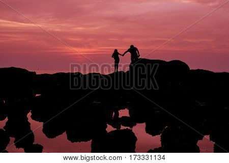 parents take care child silhouette at the sea with red and purple theme