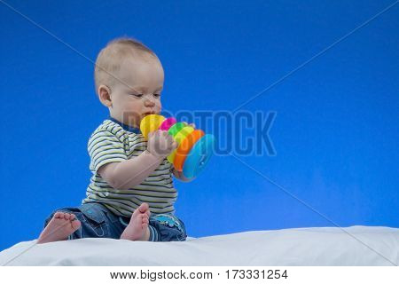 Serious little baby boy, sitting on the white blanket with a toy in hands , studio shot, isolated on blue background.
