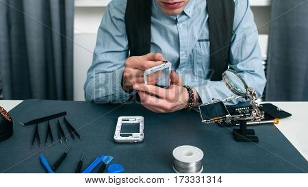 Unrecognizable man disassembling smartphone free space. Fixing process in repair shop - repairman working with broken mobile phone, special tools on workplace