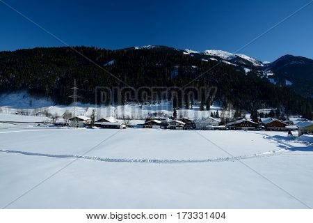 Snow on field buildings and mountain in Wagrain in Austria