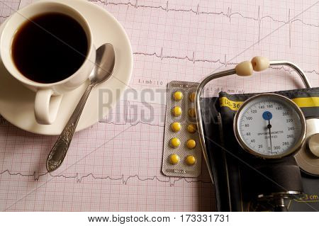Hemopiezometer for measuring blood pressure cup of coffee pills and ECG test results on the table