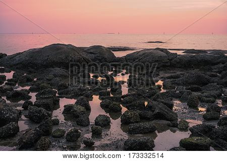 Rock at sea side with red sky
