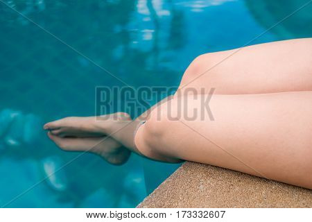 Bright knee of the girl while dip the foot in the water at the pool.