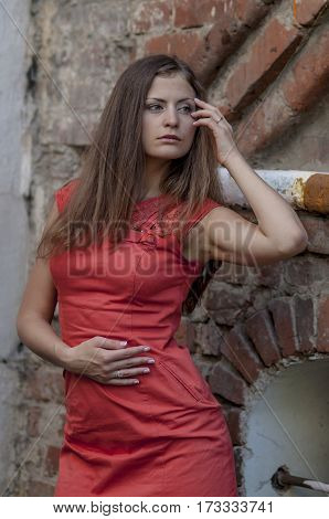 Young woman in a red dress on a background of the old wal