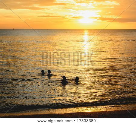 Kids play water in the sea with sunsut light at the evening.