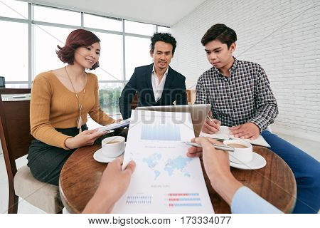 First person view of business person analyzing document at meeting
