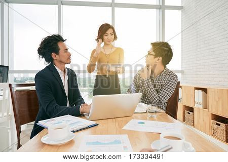 Pretty Asian business lady presenting new product at meeting