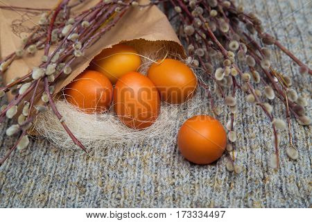 Easter colored eggs in a paper bag with branches of pussy willow, spring mood