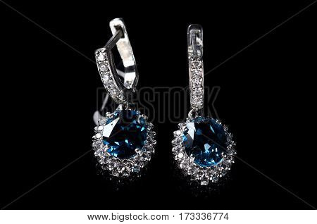 Silver Earrings With Blue Topaz Isolated On A Black Background.