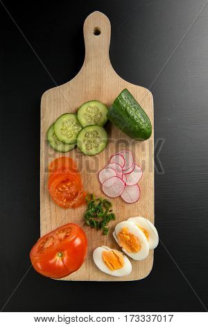 Cucumber, tomato, radish, hard-boiled egg and chives on cutting board