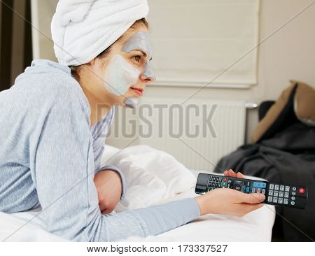 Young woman with clay mask on face watching tv at home in her bedroom.