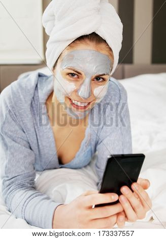 Young woman with clay mask on face using cellphone at her bedroom.
