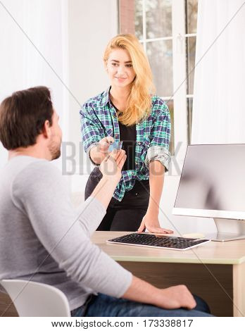 Toned of businessman giving credit card to young blond woman while sitting at table with computer on. Office interior.