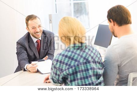Toned of salesman or manager offering contract to young couple concerning buying apartment, flat, car or automobile. Agreement or contract concept.