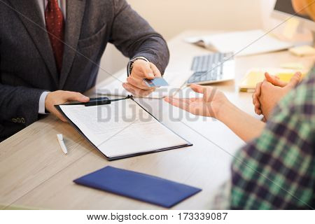 Closeup toned of salesman holding agreement or contract for customers and giving credit card. Round table meeting with manager.