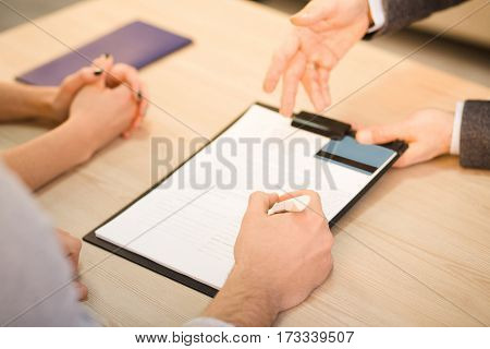 Closeup toned of salesman offering agreement or contract with credit card for buying apartment, flat, car, automobile. Businessman offering credit. Money concept. Bank concept.