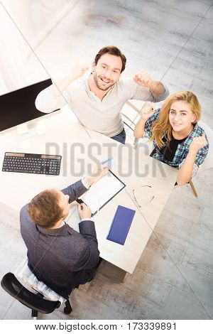 Top toned of bank officer giving credit card to young couple. Happy couple smiling and looking at camera. Dealership concept. Bank concept. Money concept.