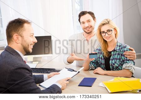 Toned of happy couple smiling and showing credit card to camera after signing agreement or contract. Dealership concept. Bank concept. Money concept.