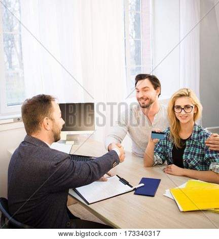 Toned of happy bank officer and customer shaking hand after signing agreement or contract. Dealership concept. Bank concept. Money concept.