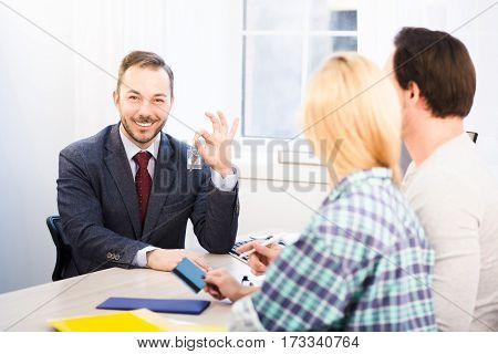 Toned of sales manager giving key to young couple. Happy sales manager showing key to camera and offering appropriate agreements or contracts for purchase or sale.