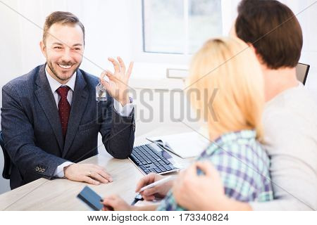Toned of handsome sales manager in business suit showing key to young couple. Happy couple in love after signing agreement or contract for purchase or sale.